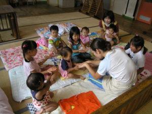 赤ちゃん達の昼寝の前に、年長児達が布団敷き、寝かしつけの手伝いにはいることがある。保育士が行う手遊びも彼等は一緒に遊んでくれる。特に、一人っ子や末っ子にとっては、乳児室の手伝いは格別のお楽しみのようだ。