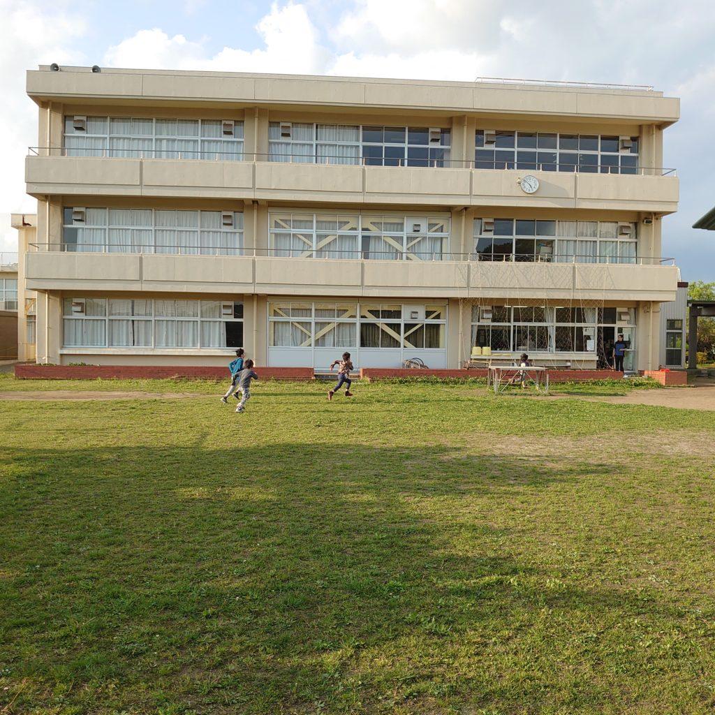 広い校庭。学校終了後の人影は、学童保育所の生徒と指導員達。 この昔ながらの校庭こそは、最新式の校庭に比べて、小学生たちにはクッションが程よいために、彼らの運動神経を絶妙に刺激し包んでくれる。